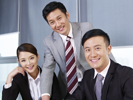 chinese business: a team of asian business people looking at camera and  smiling  Stock Photo