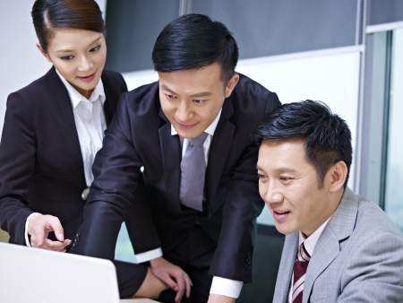 asian working woman: a team of asian business people working together in office