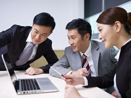laptop asian: un equipo de personas de negocios asi?ticos que trabajan junto en la oficina
