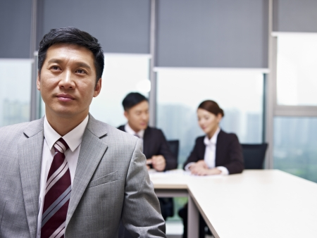 asian businessman praying for help in office photo
