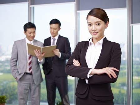 evaluating: portrait of a young asian businesswoman with colleagues in background