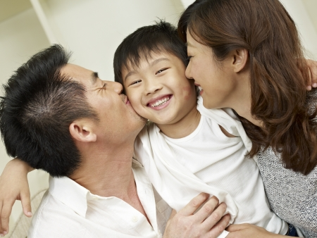 child couple: little boy kissed by mother and father  Stock Photo