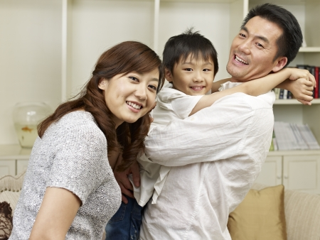 three persons: loving asian family having fun at home