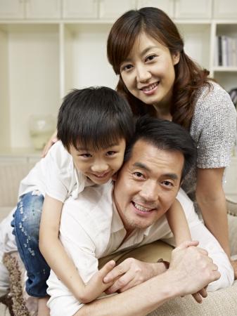 familia abrazo: amorosa familia asi?tica que se divierte en el pa?s