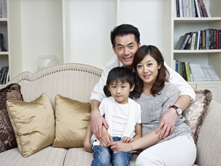portrait of an asian family sitting on couch photo