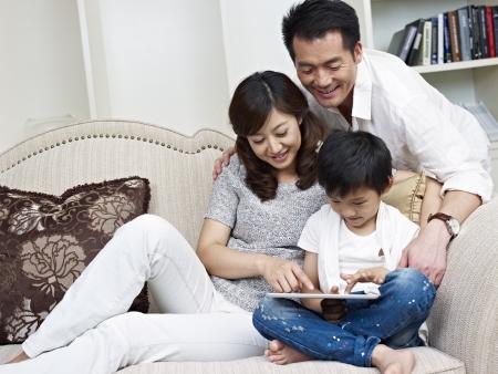 母、父と息子のタブレット コンピューターを見てします。