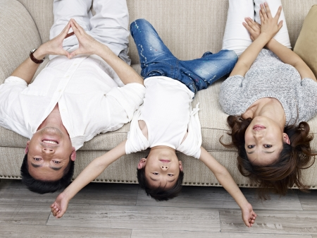 woman on couch: mother, father and son having fun at home. Stock Photo