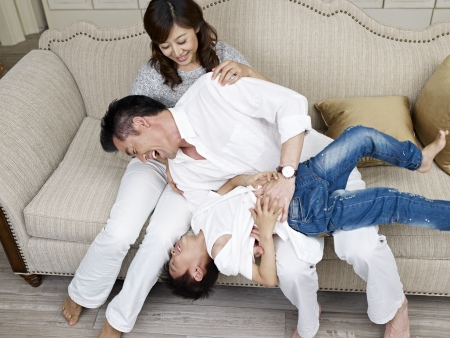 family tickle: mother, father and son having fun at home. Stock Photo