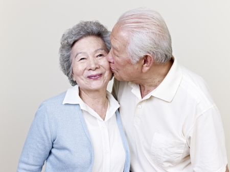 kissing couple: portrait of a senior asian couple kissing Stock Photo