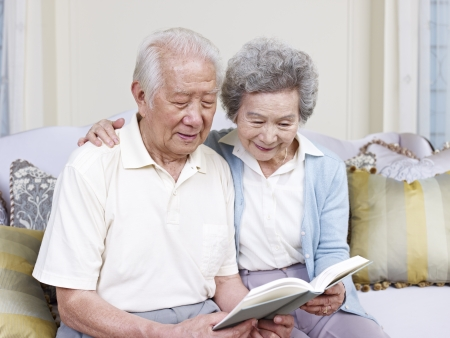 reading: senior asian couple reading a book together at home