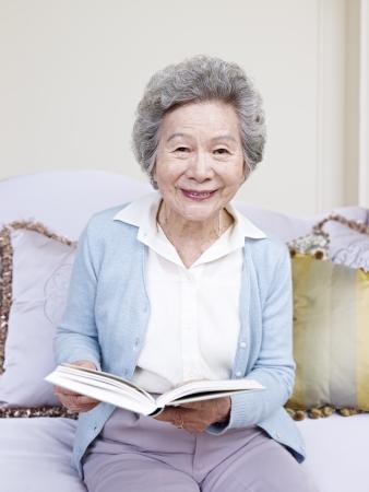 senior vrouw met een boek en glimlachend
