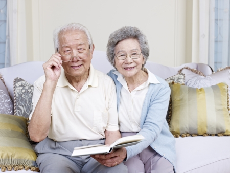 jubilados: Pares asi�ticos mayores que leen un libro juntos en casa Foto de archivo