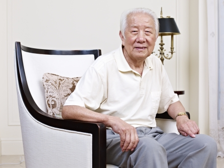old: portrait of an asian senior man sitting in an armchair