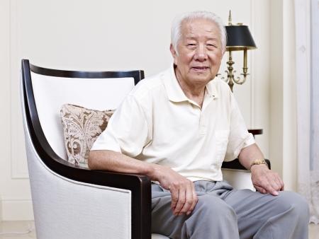 man in chair: portrait of an asian senior man sitting in an armchair