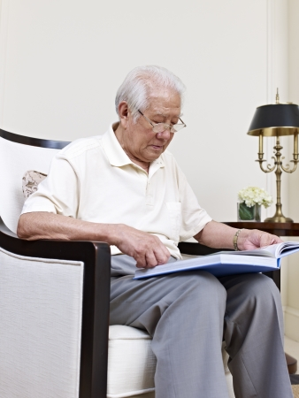 asian senior man sitting in an armchair and reading  photo