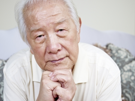 lonely person: portrait of a sad asian senior man