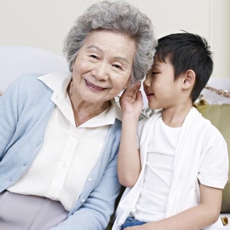 grandson telling grandma a secret  版權商用圖片