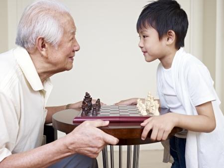 внук: дедушка и внук, глядя друг на друга, прежде чем игра в шахматы Фото со стока