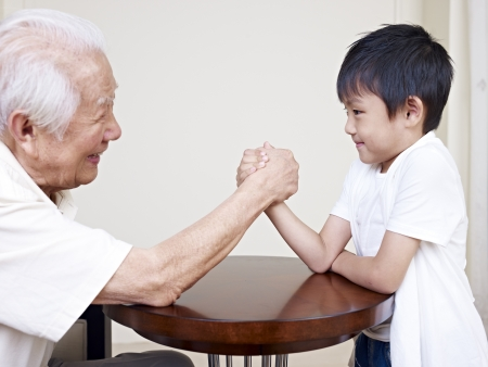 6 year old: grandpa hand wrestling with grandson  Stock Photo