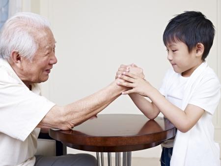 grandpa hand wrestling with grandson  Stock Photo