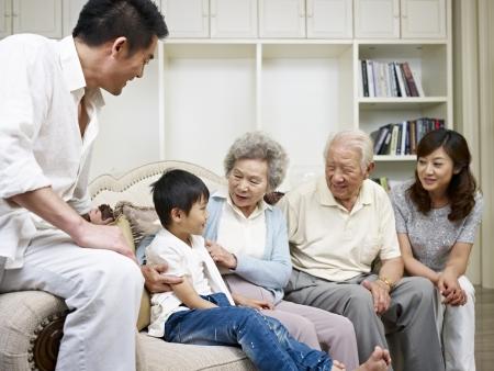 Familia asiática de tres generaciones hablando en la sala de estar