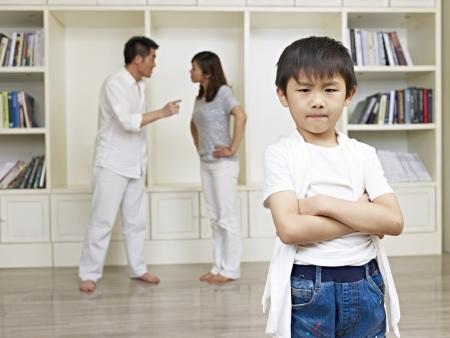 6 años de edad, muchacho asiático con pelean padres en el fondo