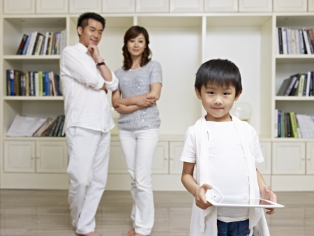 two parents: 6-year old asian boy with proud parents in background  Stock Photo