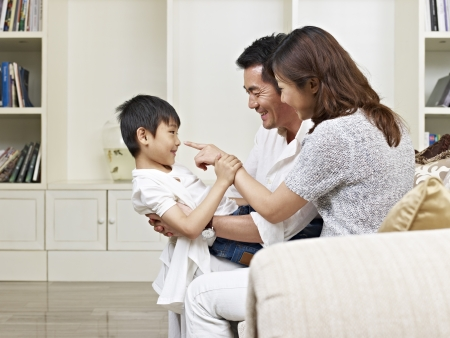 elementary age boys: asian parents and son having fun at home