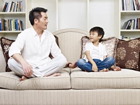 niños platicando: padre e hijo teniendo una conversación en el sofá en casa