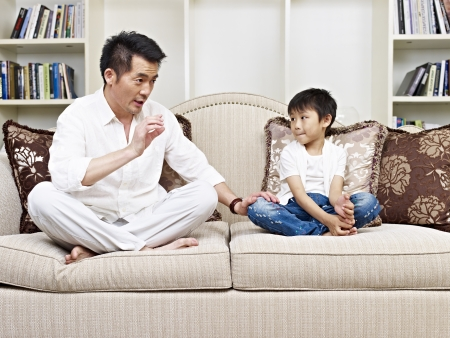 children talking: father and son having a conversation on couch at home