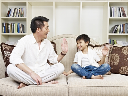 age 5: father and son having a conversation on couch at home