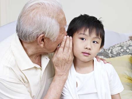 escucha activa: asi�tico abuelo nieto dici�ndole un secreto Foto de archivo