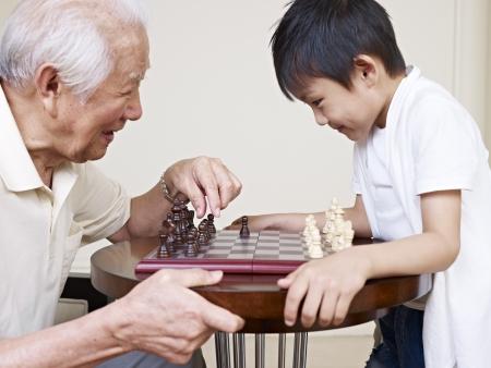 asiático abuelo y nieto jugando al ajedrez