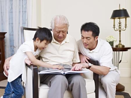внук: Азиатские сына, отца и деда, чтение книги вместе
