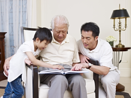 asian son, father and grandfather reading a book together  photo