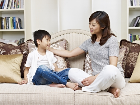 asian mother and son having a conversation on couch at home photo
