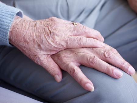 holding close: hand of an elderly woman holding the hand of an elderly man  Stock Photo