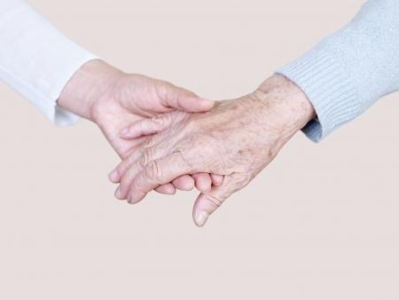 aged care: hand of a young woman holding the hand of an elderly woman