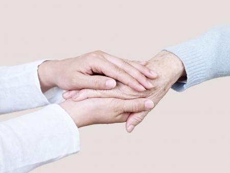 handen van een jonge vrouw die de hand van een oudere vrouw