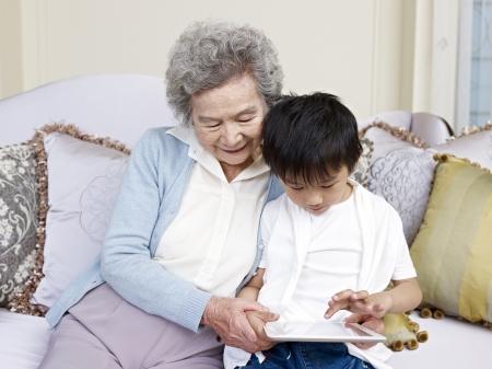 внук: бабушка и внук, глядя на планшетном компьютере вместе