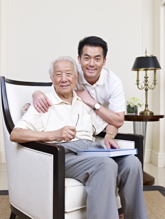 bonding: portrait of an asian senior and his adult son