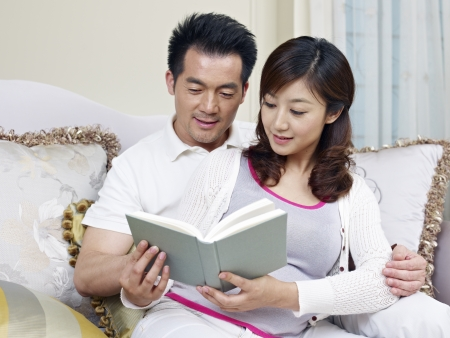 young asian couple reading a book together  photo