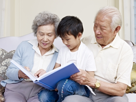 внук: бабушка и дедушка и внук, чтение книги вместе Фото со стока