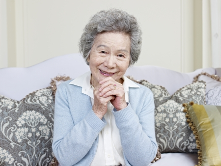 woman on couch: senior asian woman sitting on couch smiling