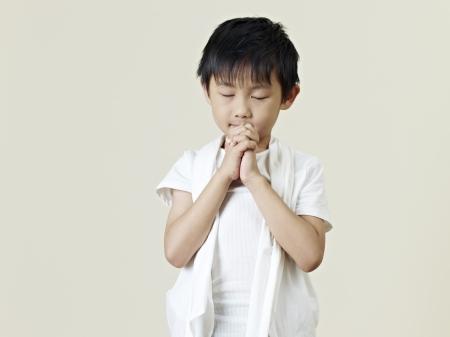 ni�o orando: seis a�os de edad del ni�o peque�o asi�tica orando Foto de archivo