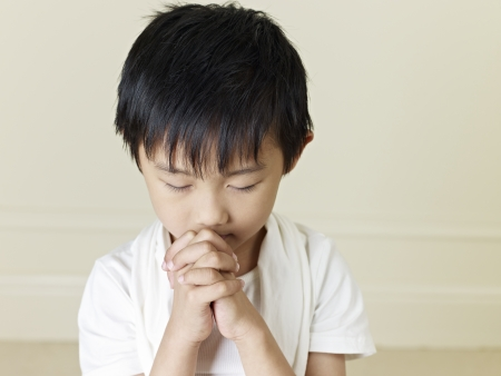 praying: six year old little asian boy praying