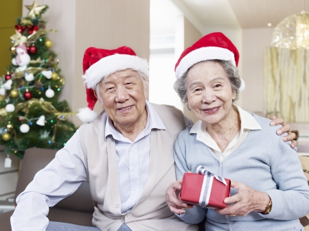 Portrait of an Asian senior couple with Christmas hats and gifts  photo