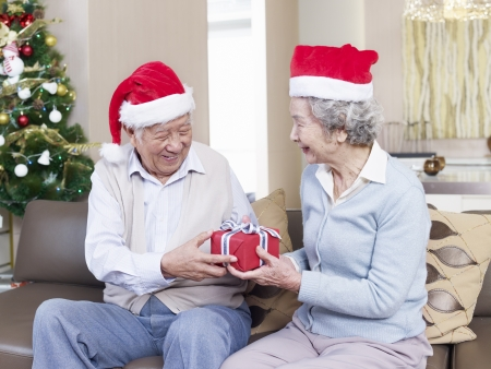 Asian senior couple with Christmas hats exchanging gifts  photo