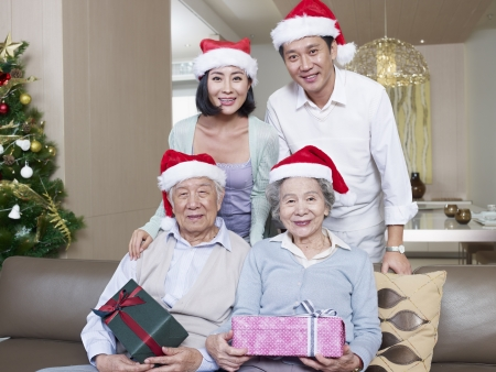portrait of an Asian family with Christmas hats and gifts