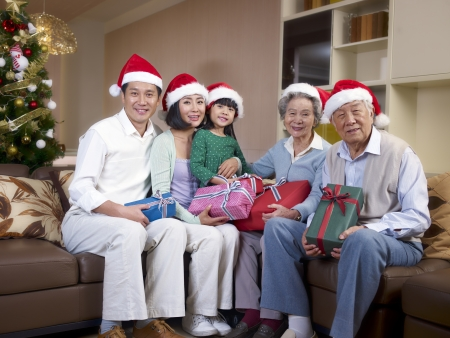 headwear: Home portrait of an Asian family with Christmas hats and gifts